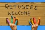 """Refugees welcome - Hände mit bunten Fingern halten ein Pappschild mit der Aufschrift """"Flüchtlinge willkommen"""""""